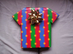 A wrapped gifts shaped like a t-shirt.
