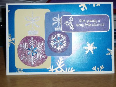 this is the first card i actually put together. when i was cutting the cardstock to make the background i ended up with a long strip that i couldnt use, and remembered my snowflake punch, so i had a go with that to see how it would look. To my delight, it looked wonderful, so i stamped some more, and appled a shiny jewelled sequin type thing to the middle.