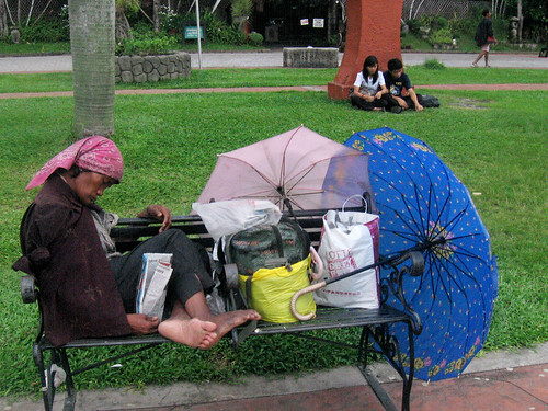 An homeless old woman rests on a bench in a public park in Luneta Park Manila Philippines Buhay Pinoy  Ngayon Filipino Pilipino  people pictures photos life Philippinen public park personal belongings homeless