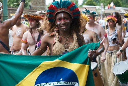 A lady dressed in carnival clothing holds a Brazilian flag