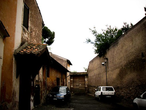 벽을 마주하고 집 몇 채가 서 있다. 주차된 차가 몇 대 있다.
