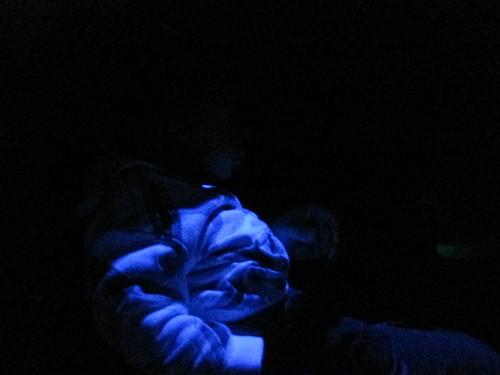 Emmett in his white sweater under the black light