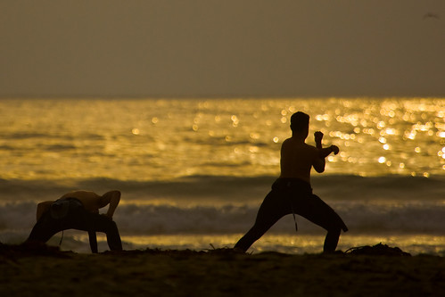Two Surfers do Pre-stretches on Morro Strand State Beach prior to a sunset surf session by mikebaird