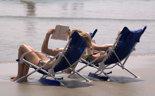 photo of two beautiful young women at the beach reading next to the water