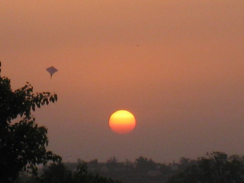 A kite flies high as the sun sets over Agra