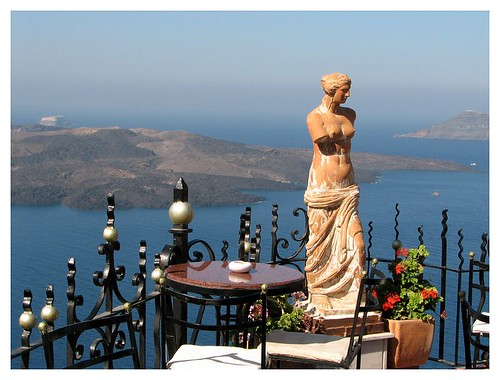 A beautiful statue on the balcony of a restaurant by you.