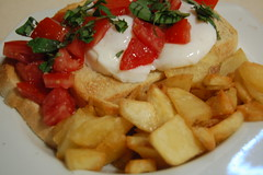 Poached eggs, tomato and basil with fried potatoes