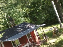 En pappa på taket till gäststugan, en mamma sågar ved