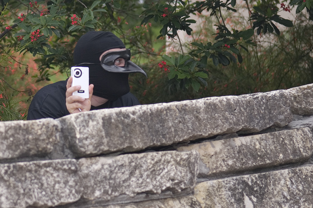 Image of a man in a mask taking a photo over a wall