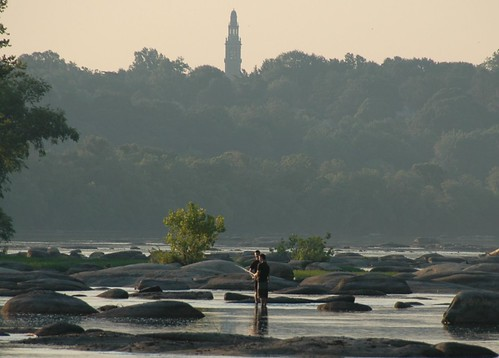 a photo of two boys fishing in the James River at dawn
