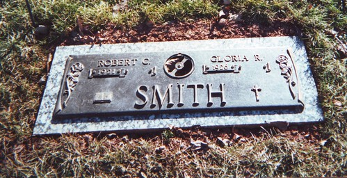Metal grave marker for Robert C. and Gloria R. Smith, born 1921 and 1926 respectively, a rose on each side, and then an open Bible below his name and cross below hers