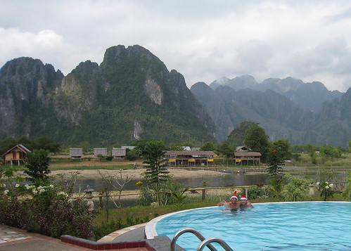 Christmas morning in the pool with my travel buddy Chris, with the beautiful limestone mountains of Vang Vieng in the background