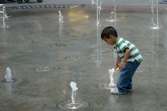 A child plays in a bubbling fountain