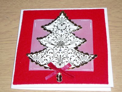 background is red felt, the pinkish square beneath the tree is parchment paper