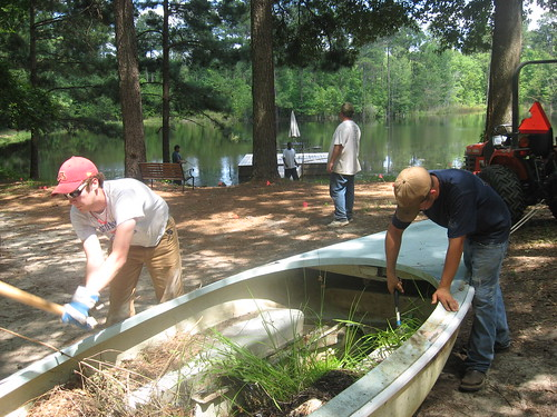 Damien and Kyle hacking up the old sailboat to sink to the bottom of the pond for fish hatchery.