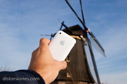 iPhone blanco con molino de viento al fondo