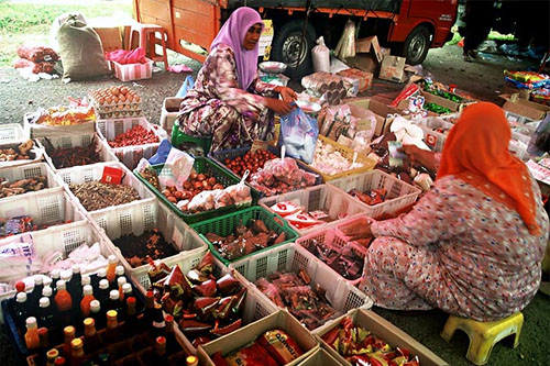 A lady trader with her customer at the Kuala Besut weekly market