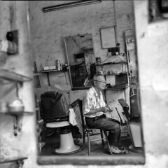 a glimpse inside a barber's every day life (lcy) Tags: travel bw 6x6 tlr monochrome mediumformat candid urbandecay ishootfilm unesco worldheritagesite squareformat barber malaysia nostalgic dailylife oldpeople mirrorshot melaka malacca 120mm oldshop  peopleportrait kodak400tmax vanishingtrade rolleiflex28e dyingtrade schneiderxenotar canoscan8800f traditionaltrade