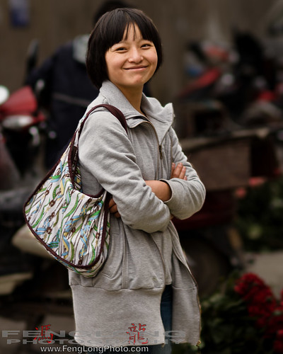 Young girl selling flowers at the flower market in downtown Shanghai