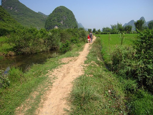 Pauline and the kids walk on a path through rice fields beside the Li River, south of Yangshuo, China.