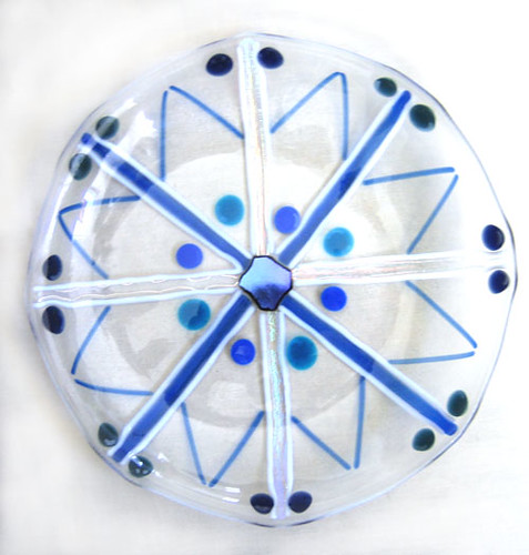 a fused glass snowflake plate with dichroic center