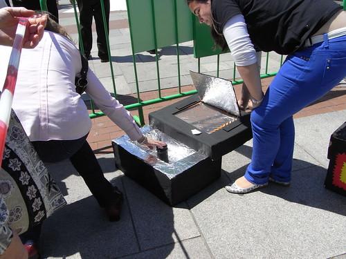 Alumna de instituto divulgando la estructura de una cocina solar.