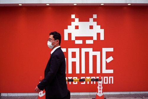 A man in a medical mask passes in front of an arcade in Osaka, Japan, at the height of the Kansai A/H1N1 Influenza scare, May 2009.