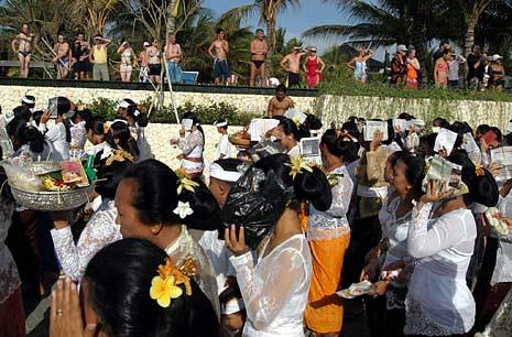 Turis-turis asing menyaksikan umat Hindu yang melintas di Pantai Legian, Bali untuk melaksanakan Upacara Melasti