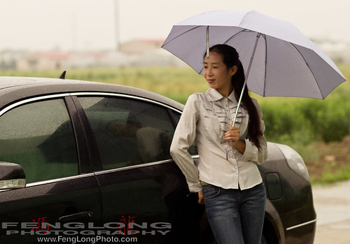 Angela - Xiao Zou outside a car with umbrella