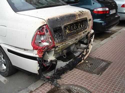 El coche que estaba aparcado junto a los contenedores quemados