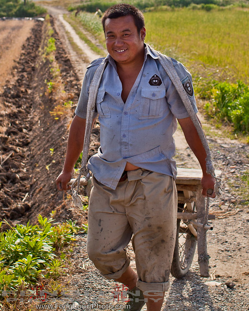 Farmer carrying cement to build a ditch in Shanghai