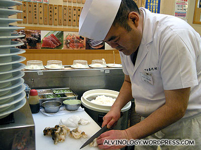 Sushi chef slicing up a fresh piece of abalone