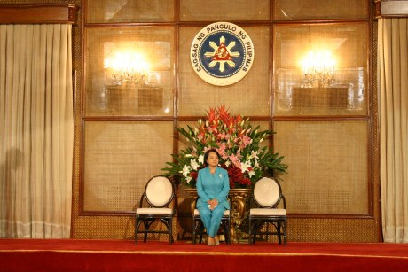 The President all alone on the stage while waiting for the Awarding Ceremonies for Lupong Tagapamayapa and Kalasag to start.  Take note of the towering flower arrangments behind her.