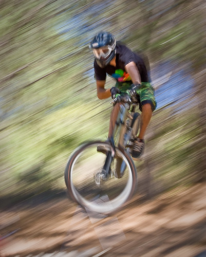 Panned photo of airborne mountain biker against a blurred background