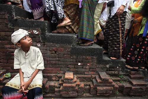 Seorang anak menunggu giliran antri memasuki Pura Pangrebongan untuk bersembahyang saat Hari Raya Kuningan di Denpasar, Bali.
