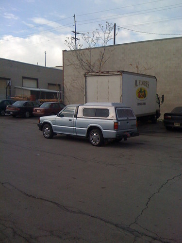 Reys silver Mazda pickup truck parked facing the truck docs of M. Flores productos