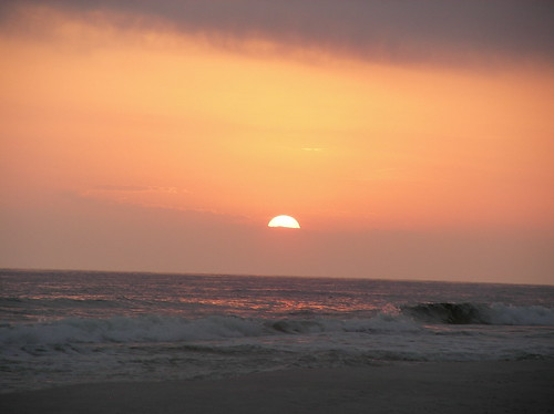This photo shows the sun starting to set above the beach