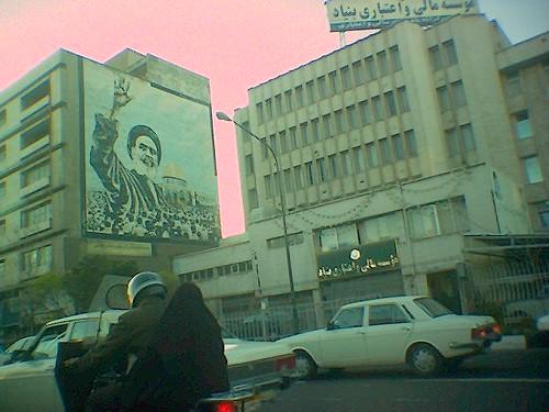 Hombre+y+mujer+con+chador+en+moto+con+cartel%C3%B3n+de+Jomeini+al+fondo