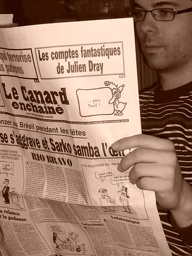 Man reading Le Canard Enchainé