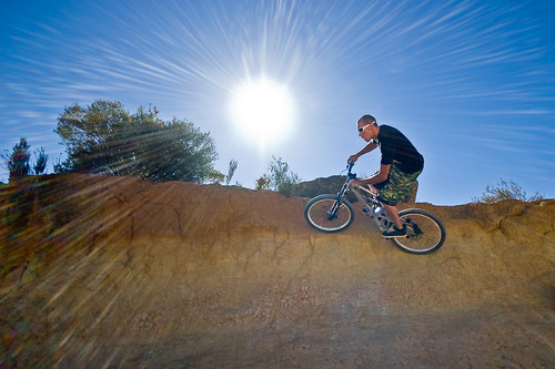 Mountain biker riding a wall against a blazing sun