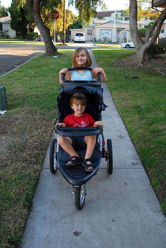 two cute kids showcase a new stroller
