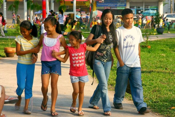 Big Sister and Little Sisters with Big Brother strolling happily in the GenSan Park.