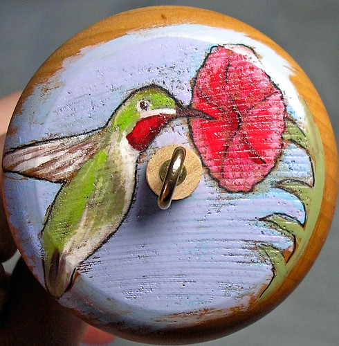 Photo of top view of handpainted whorl, painting of a ruby throated hummingbird in flight, feeding from a red morning glory