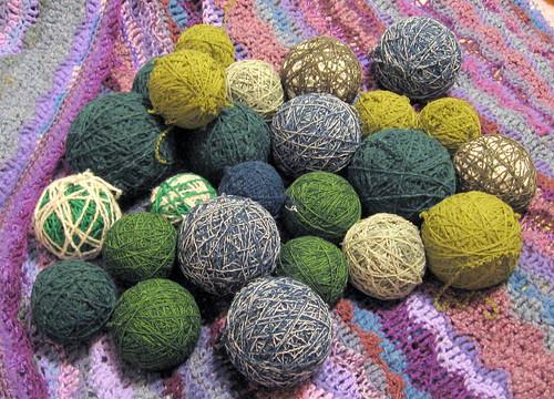 balls of green yarn on a purple blanket