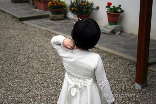 Flower girl scratching an itchy tag on a pretty white dress at a wedding in Tuscany
