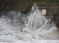 Photograph of wave crashing against sea wall.