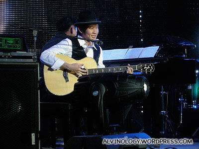 JJ Lin singing and on the guitar; Kheng Long on the piano