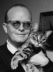 Truman Capote cuddles kitty 1967