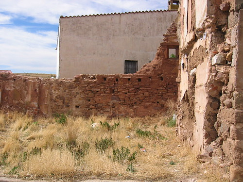 Crumbling facade on a Spanish house and an old brick wall