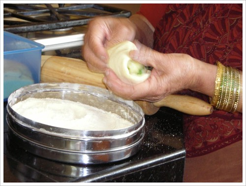Champa folding the potato filling into the dough by you.